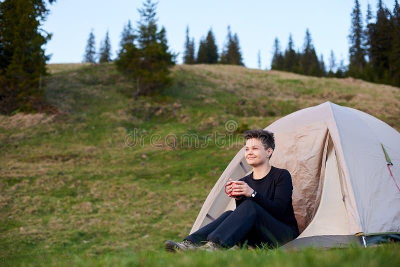 Chá bebendo do caminhante fêmea feliz na barraca dianteira do acampamento fotos de stock