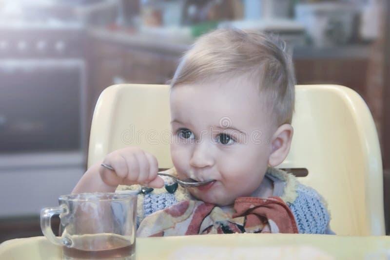 Chá bebendo do rapaz pequeno bonito de uma caneca com uma colher ao sentar-se em uma cadeira foto de stock