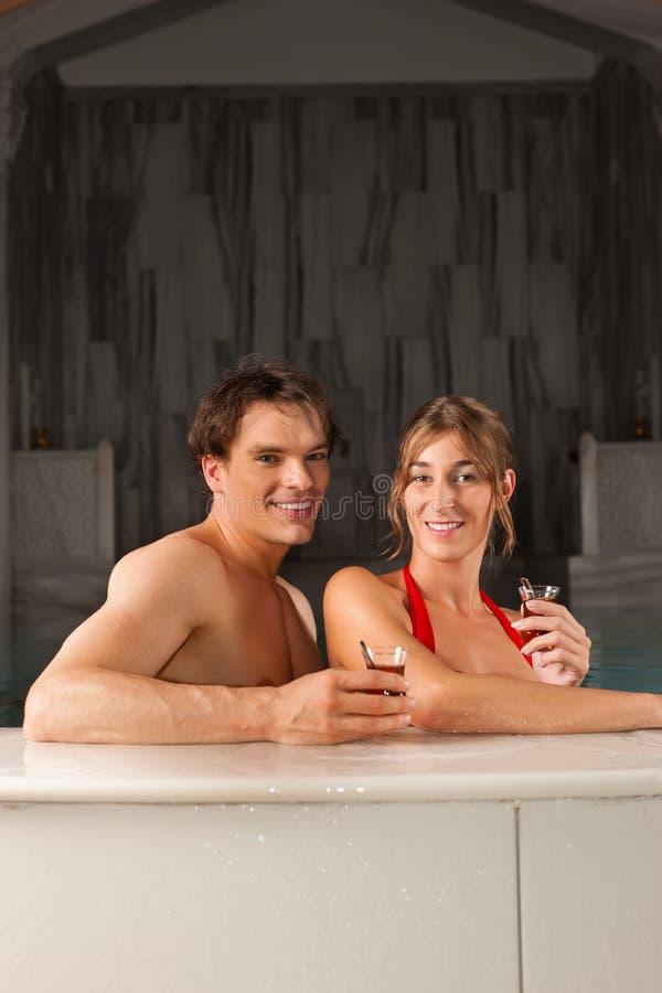 Chá bebendo dos pares na piscina fotografia de stock royalty free