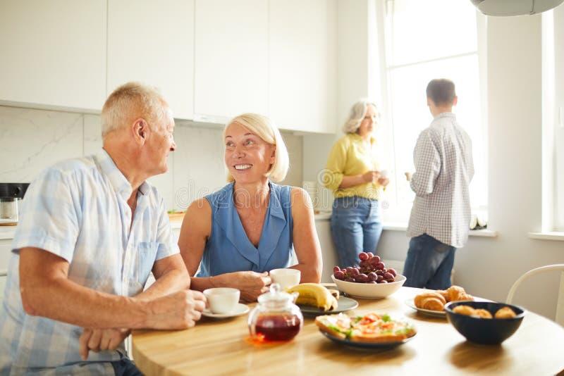 Chá bebendo dos povos maduros na cozinha imagem de stock