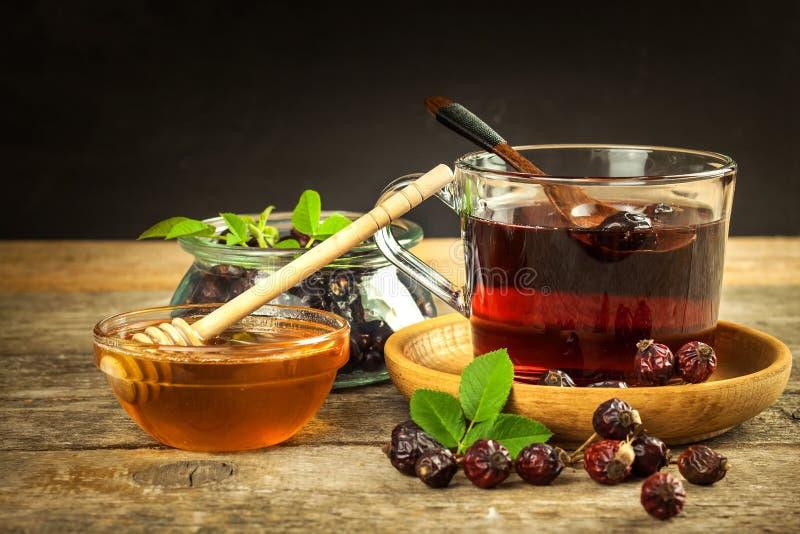 chá Casa-feito do rosehip Cura tradicional para frios e gripe Baga secada em uma tabela de madeira Chá quente do rosehip Chá do i imagem de stock