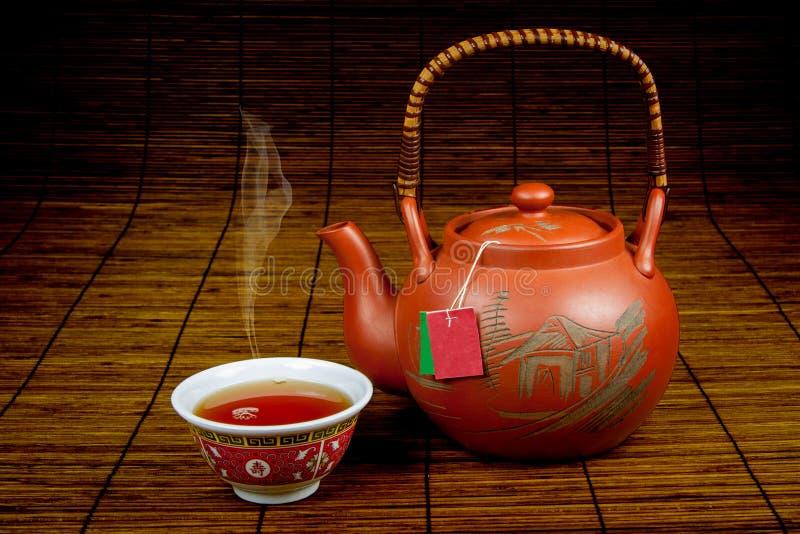 Chá chinês de derramamento em um cup-1 foto de stock royalty free