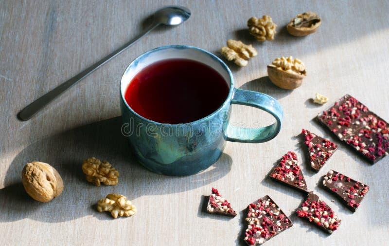 Chá, chocolate, porcas e framboesas da framboesa em uma tabela de madeira, foco seletivo foto de stock