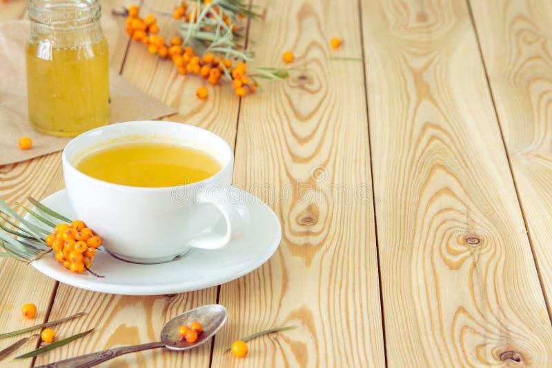 Chá com as bagas alaranjadas do mar-espinheiro cerval em um copo e em um mel orgânico fotos de stock
