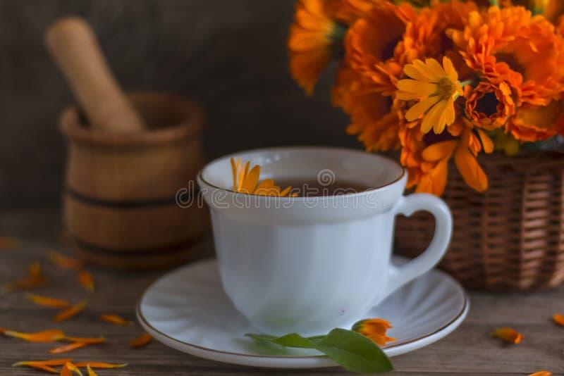 Chá com calendula em uma cesta em um fundo de madeira e almofariz com o pilão para ervas de moedura foto de stock royalty free