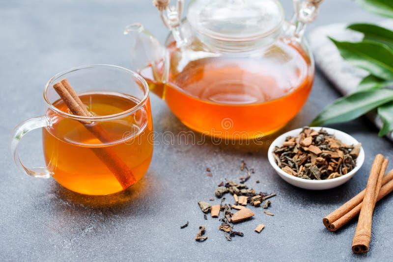 Chá com canela no copo e no bule de vidro no fundo de pedra cinzento fotografia de stock royalty free
