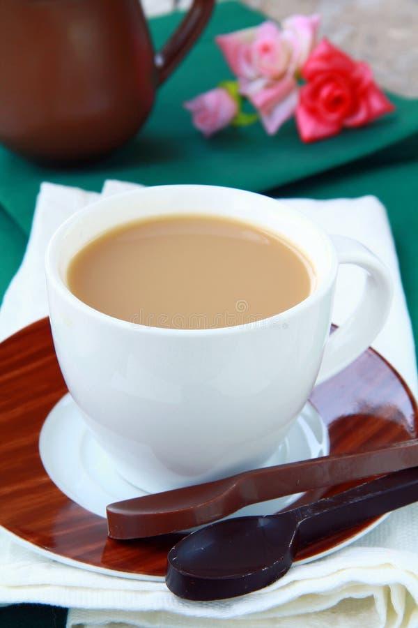 Chá com leite em um copo branco imagem de stock
