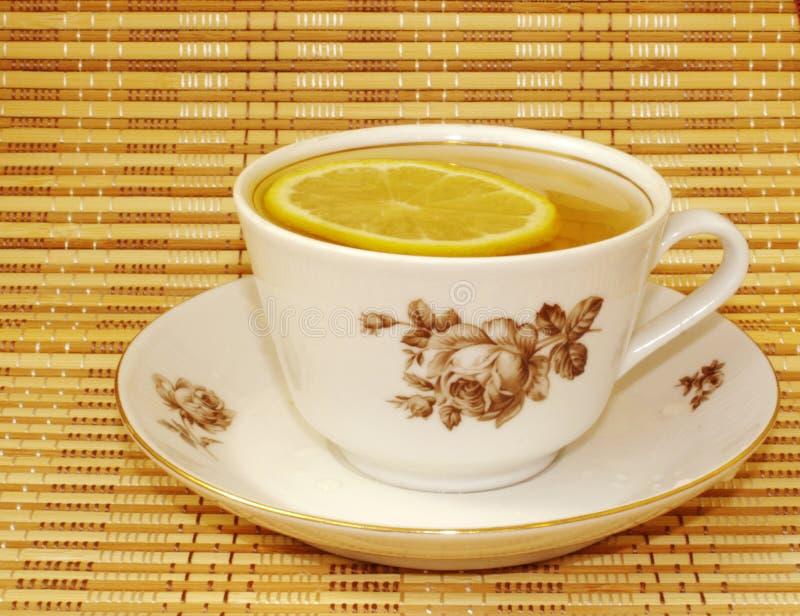 Chá com limão em um copo com um teste padrão marrom imagem de stock
