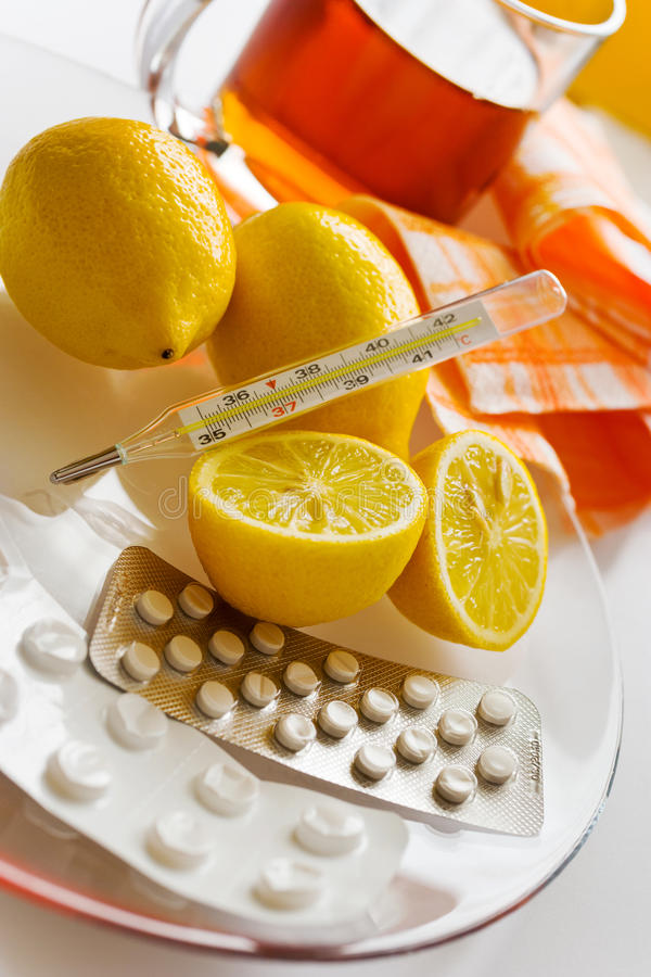 Chá com limões e comprimidos da gripe com termômetro - remédio do grippe imagem de stock
