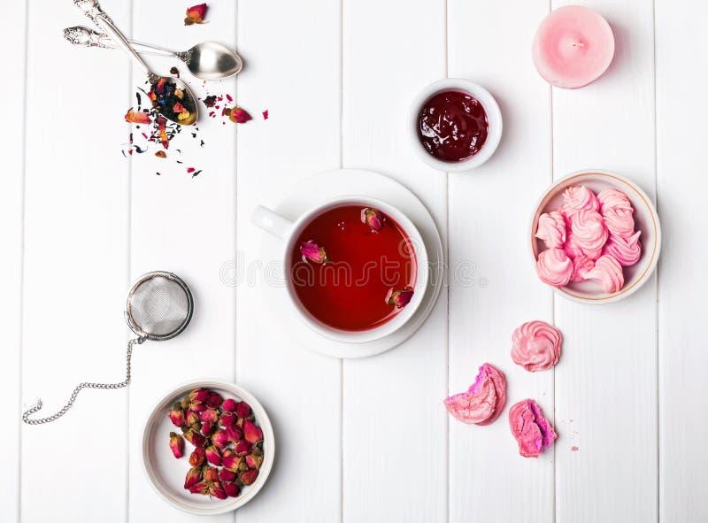 Chá com rosas secadas, doce e pastelarias cor-de-rosa pequenas no t branco fotografia de stock