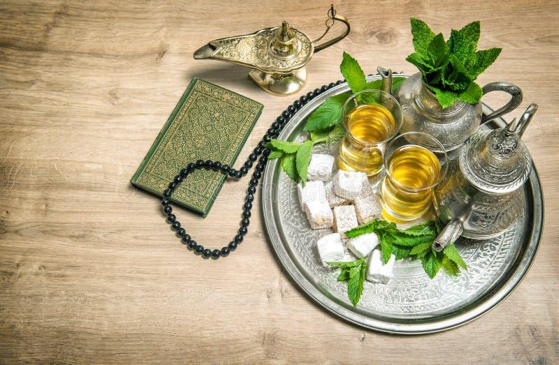 Chá da hortelã, prazer, lanterna árabe, quran do livro sagrado e rosário imagens de stock