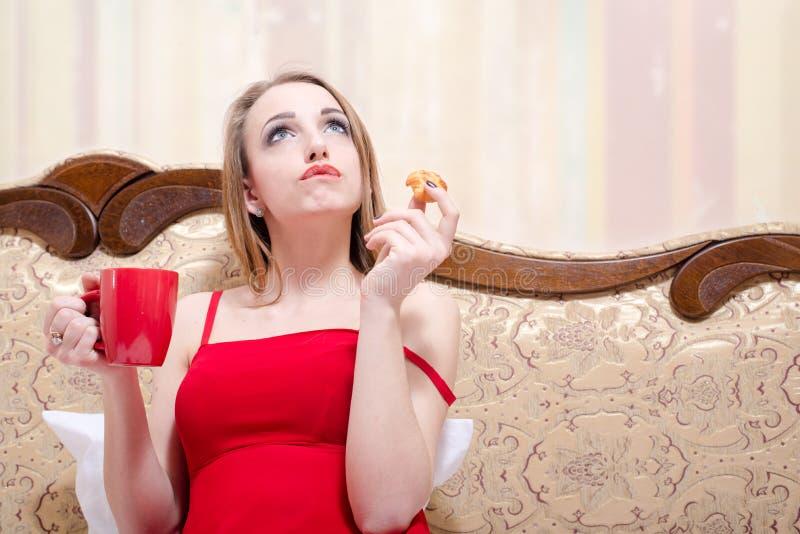 Chá da jovem mulher loura e comer bolo bebendo sobre fotografia de stock royalty free
