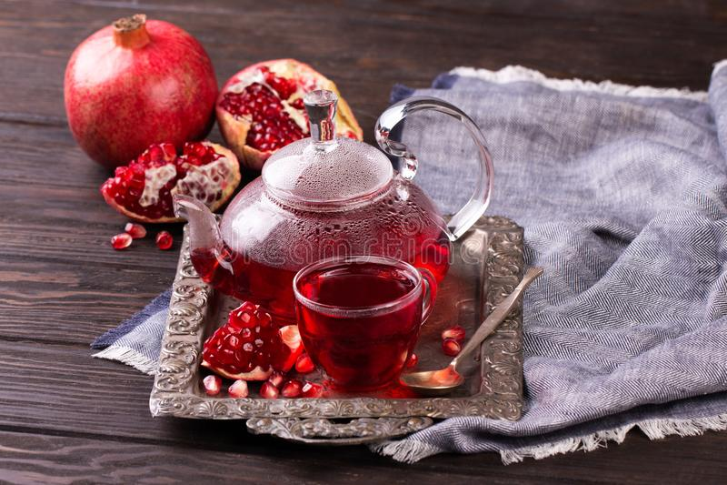 Chá da romã do fruto em um bule e em um copo fotografia de stock