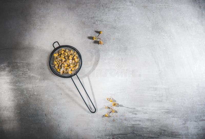 Chá de camomila com flores soltas numa palheta escura sobre mesa cinza fotos de stock royalty free