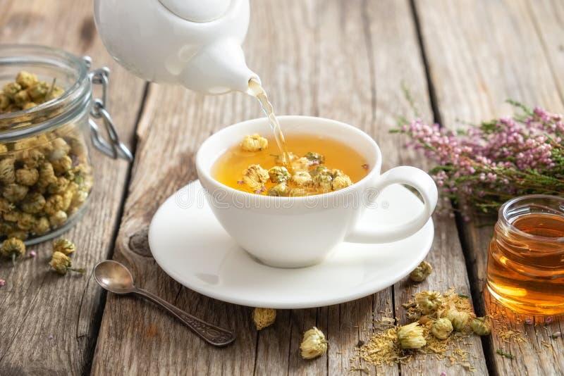 Chá de camomila saudável derramado no copo branco Bule, frasco do mel, grupo da urze, frasco de ervas da margarida fotos de stock