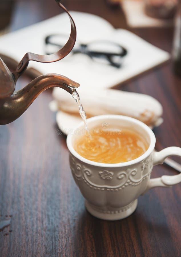 Chá de derramamento da chaleira de cobre antiquada a colocar na tabela de madeira imagem de stock