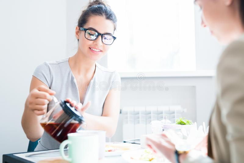 Chá de derramamento da jovem mulher no café foto de stock