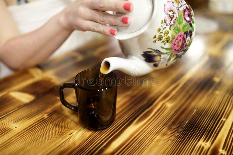 Chá de derramamento da mulher do bule cerâmico imagem de stock