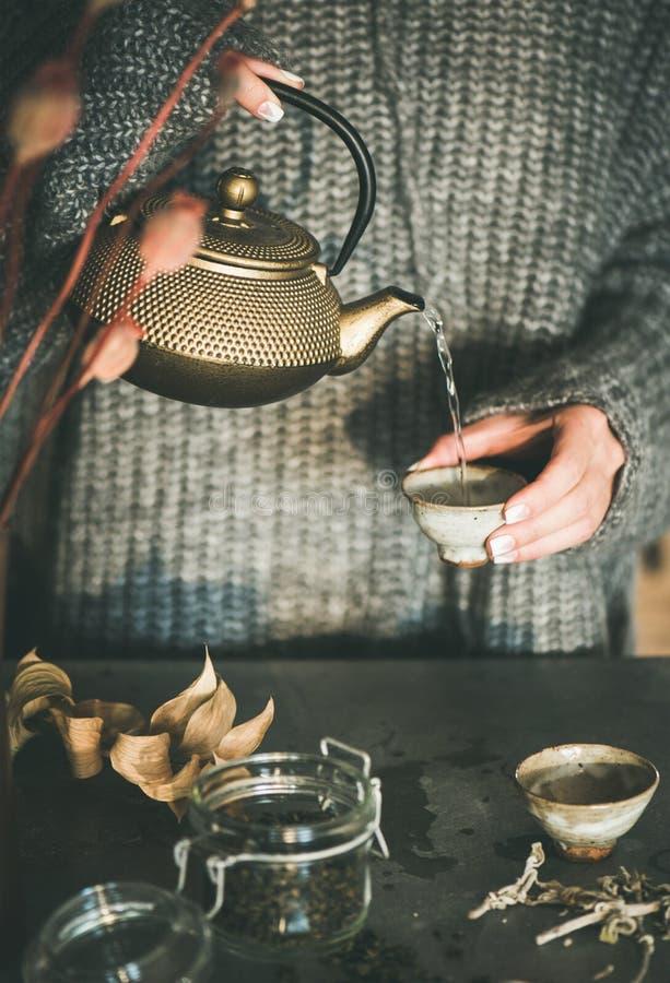 Chá de derramamento da mulher do bule dourado no copo fotos de stock royalty free