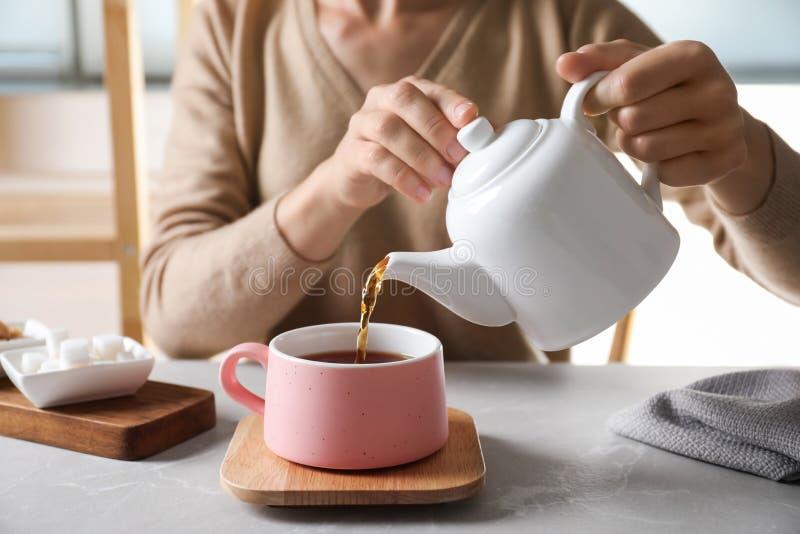 Chá de derramamento da mulher no copo cerâmico na tabela, imagem de stock