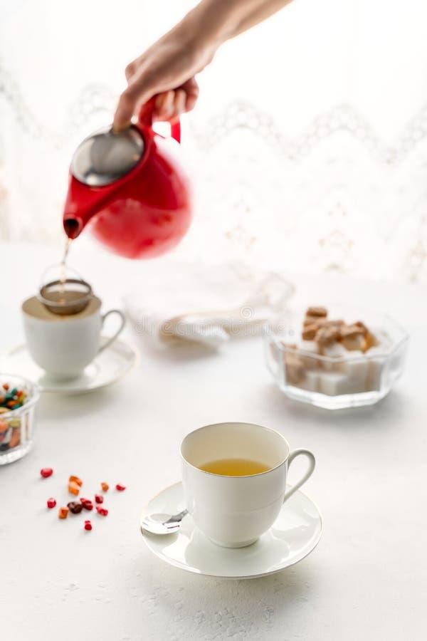 Chá de derramamento do hande da mulher do bule vermelho, copos de chá brancos, posição do açucareiro na tabela branca fotos de stock
