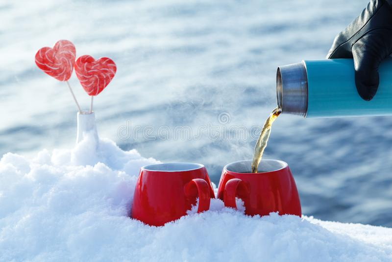 Chá de derramamento de uma garrafa térmica no em um piquenique no dia de Valentim Canecas vermelhas com chá quente, corações dos  fotos de stock
