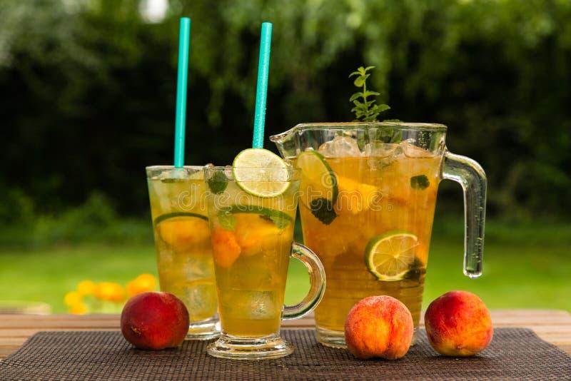 Chá de gelo caseiro do pêssego com cal e erva-cidreira fotografia de stock royalty free