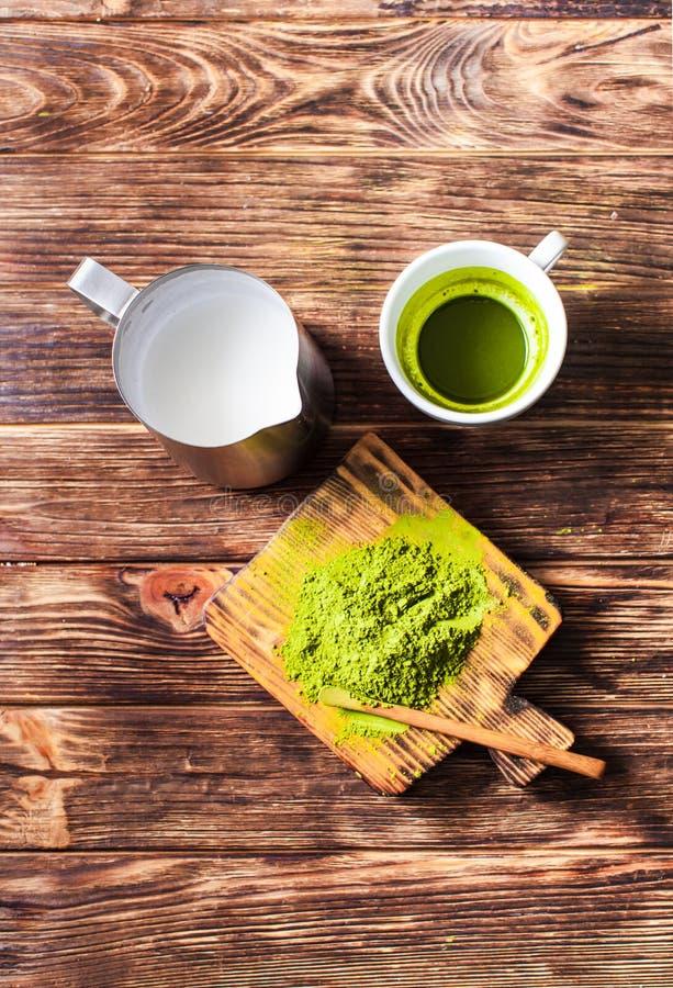 Chá de Matcha com o jarro pulverizado de chá verde e de leite em uma placa de madeira rústica escura imagem de stock royalty free