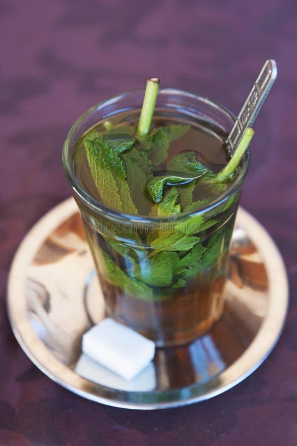 Chá do Berber em um copo de vidro com os pires da colher e da prata com um cubo do açúcar fotografia de stock