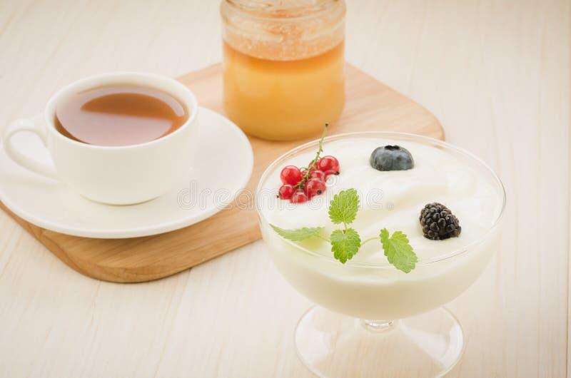 chá do copo, iogurte com chá das bagas e do frasco/copo do mel, iogurte com bagas e frasco do mel no fundo de madeira Foco seleti fotos de stock