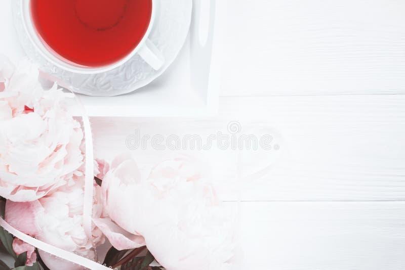 Chá do fruto e peônias cor-de-rosa das flores no fundo de madeira branco Vista superior imagens de stock royalty free