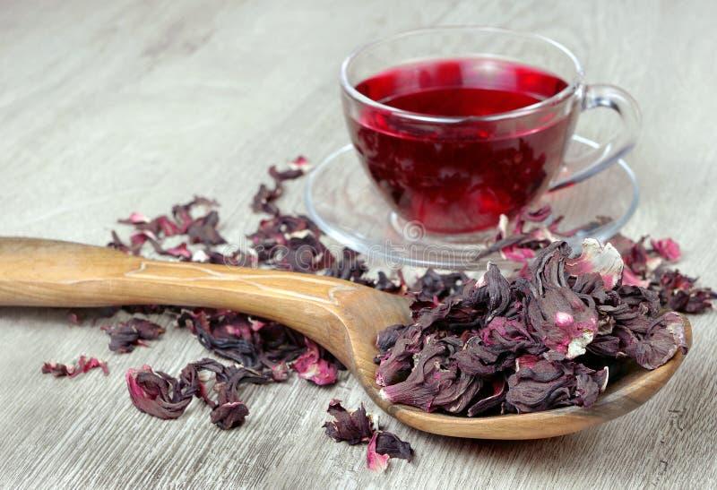 Chá do hibiscus Chá do hibiscus em uma colher de madeira em um fundo de um copo do chá fresco Chá da vitamina para o frio e a gri imagem de stock royalty free