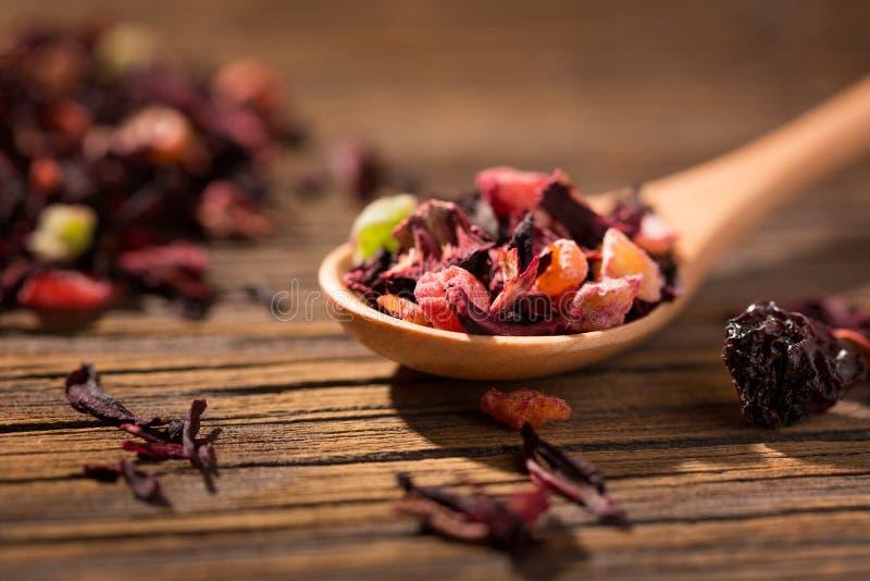 Chá do hibiscus Mistura seca de chá vermelho erval e do fruto sobre a superfície de madeira foto de stock