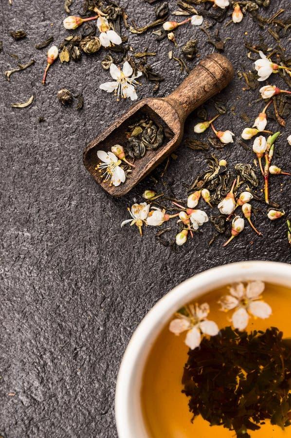 Chá do jasmim com colher de madeira, copo e as flores frescas no fundo de pedra preto foto de stock royalty free