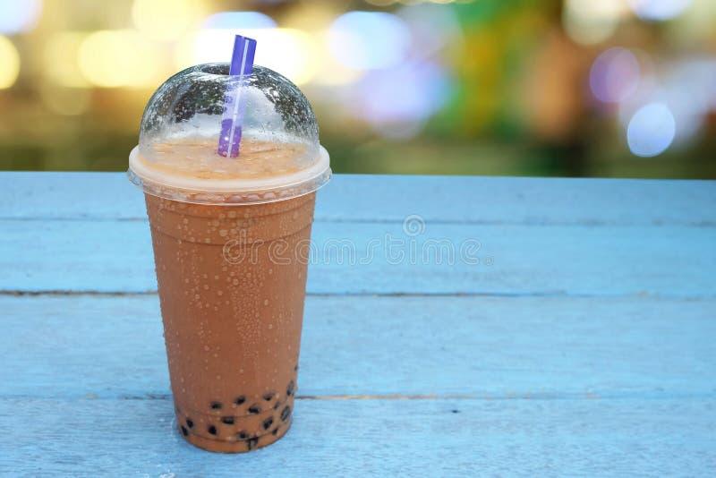 Chá do leite da bolha da pérola com gelo no copo plástico em de madeira imagem de stock royalty free