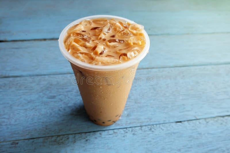 Chá do leite da bolha da pérola com gelo no copo plástico em de madeira fotografia de stock
