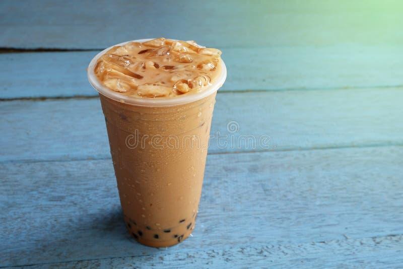 Chá do leite da bolha da pérola com gelo no copo plástico em de madeira fotos de stock