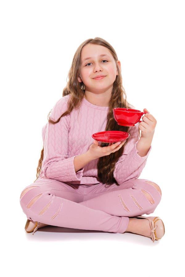 Chá do pulso de disparo do ` de cinco o Uma menina de sorriso bebe uma bebida quente ao sentar-se no assoalho Isolação no branco imagens de stock