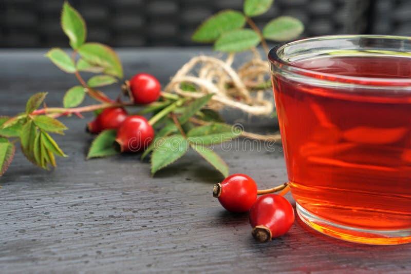 Chá do quadril de Rosa com a baga orgânica no fundo preto imagens de stock royalty free
