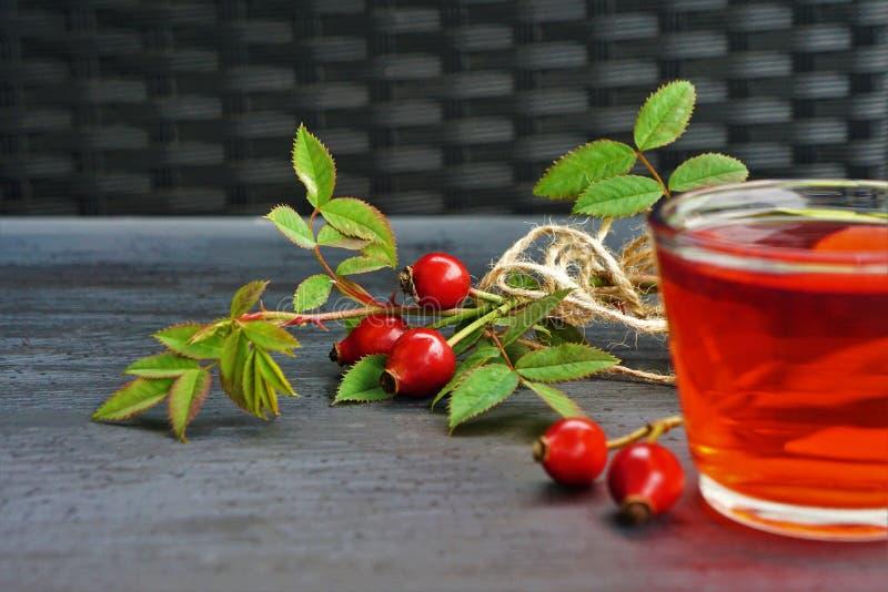 Chá do quadril de Rosa com a baga orgânica no fundo preto fotografia de stock royalty free