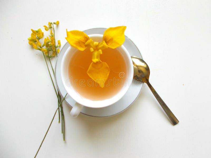 Chá em um copo branco com flores amarelas fotografia de stock