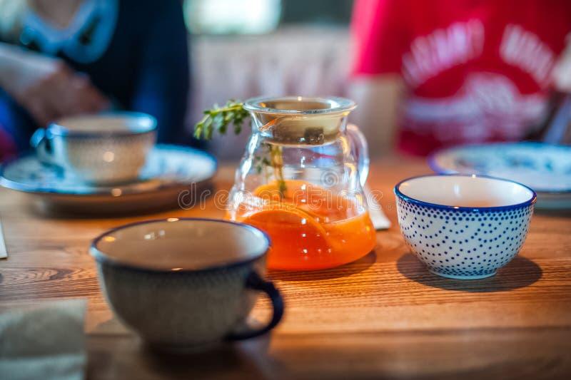 Chá em um grande potenciômetro com um ramo Chá com manga e laranja na tabela em um café fotos de stock