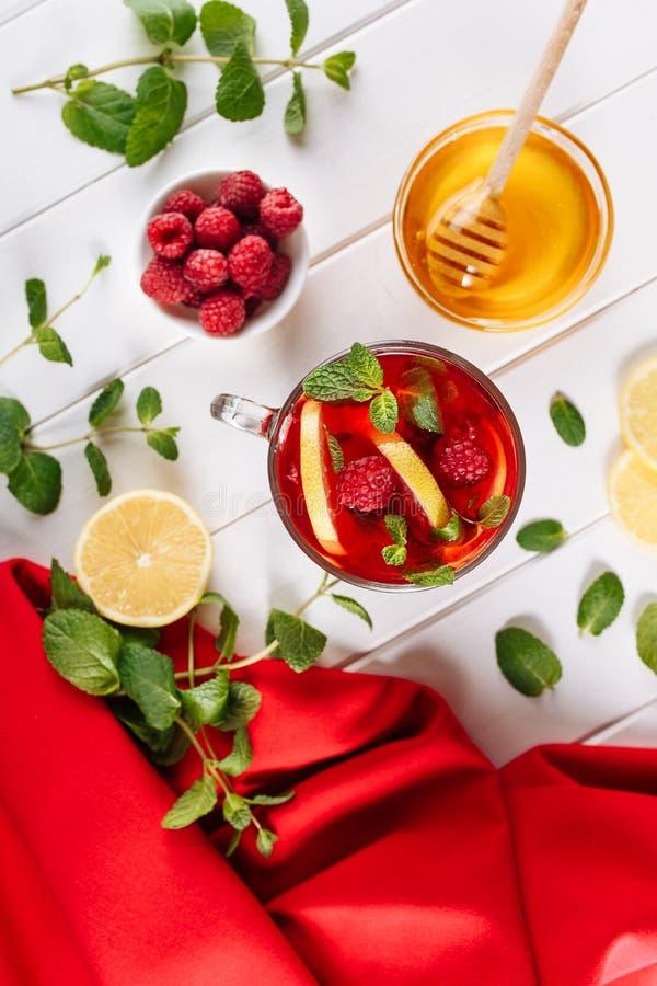 Chá encarnado com a framboesa no fundo de madeira branco Decorado com folhas, limão e mel de hortelã Vista superior com c?pia imagens de stock