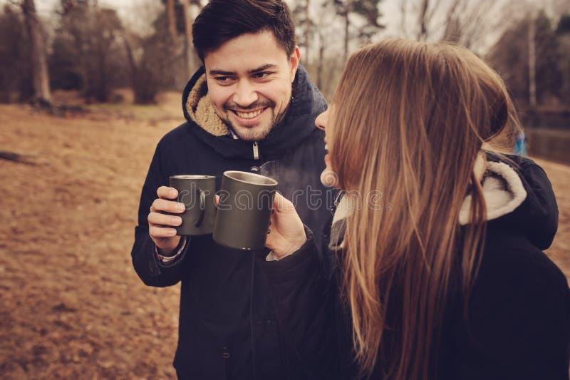 Chá exterior dos pares novos loving junto, bebendo feliz da garrafa térmica, acampamento do outono imagens de stock royalty free