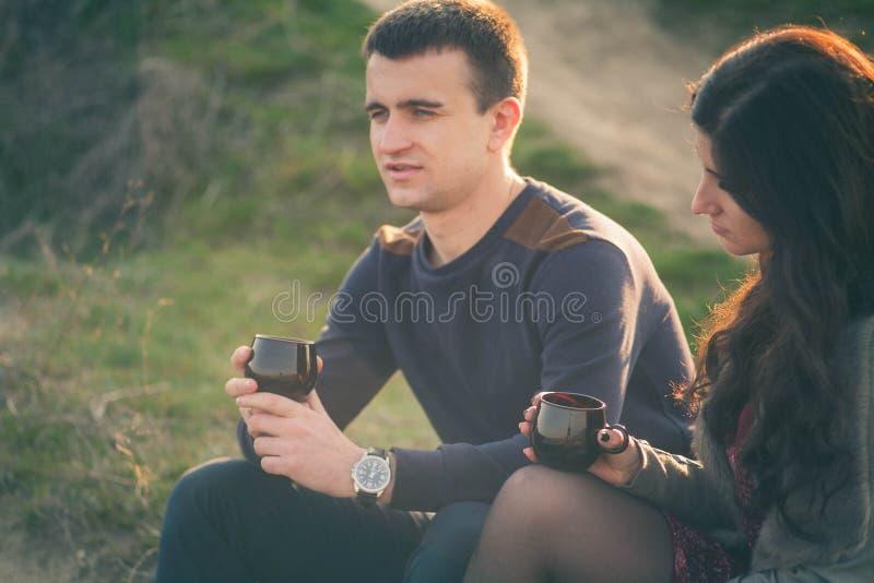 Chá exterior dos pares novos loving junto, bebendo feliz Um indivíduo com uma menina no lago no por do sol bebe o chá foto de stock