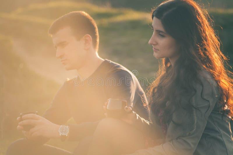Chá exterior dos pares novos loving junto, bebendo feliz Um indivíduo com uma menina no lago no por do sol bebe o chá fotos de stock royalty free
