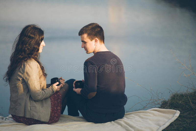 Chá exterior dos pares novos loving junto, bebendo feliz Um indivíduo com uma menina no lago no por do sol bebe o chá foto de stock royalty free