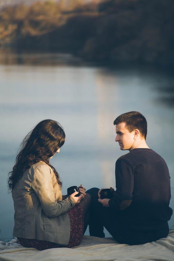 Chá exterior dos pares novos loving junto, bebendo feliz Um indivíduo com uma menina no lago no por do sol bebe o chá imagens de stock royalty free