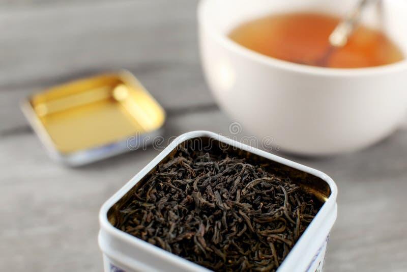 Chá fraco preto na lata do metal, com o copo borrado do drin ambarino quente imagem de stock