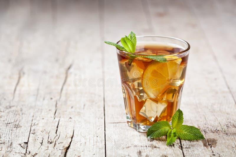 Chá gelado tradicional com limão, folhas de hortelã e gelo no vidro no fundo de madeira rústico da tabela fotografia de stock